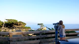Girl Looks through Telescope at Lone Cypress