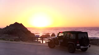 Jeep Parked by Ocean at Sunset by Aerial Drone