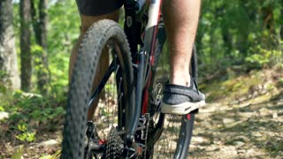 Man Pedaling Bike in Forest, Close-up Shot