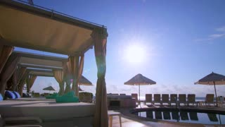 Perfect Sunset over Infinity Pool with Umbrellas Slow Motion Tracking Shot