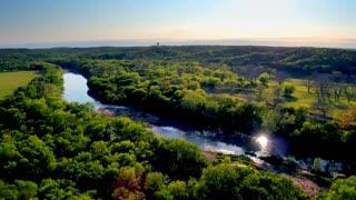 River Runs Through Green Trees Next to Golf Course