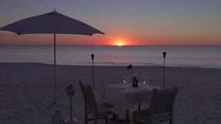 Romantic Tables and Chairs On the Beach at Sunset
