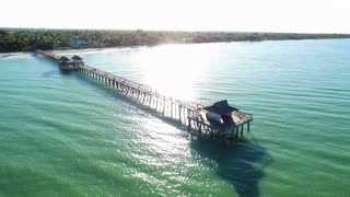Small Pier in Calm Ocean with Sun Reflecting on Water
