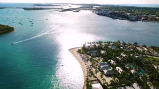 Tropical Beach Town with Boat and Jet Ski Passing