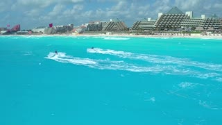 Two Jetskis in Blue Ocean in front of Resort Hotels