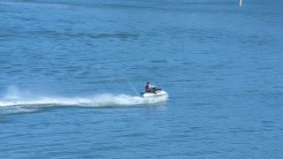 Wave-runner weaves through blue ocean water