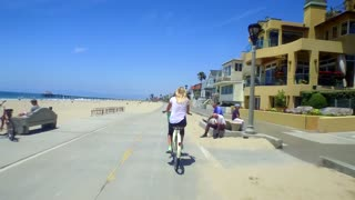 Woman rides bike alongside beach homes and beach on sunny day