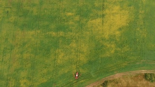 Aerial Shot of a tractor in field spraying rapeseed view from above as sprayer arms extend