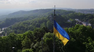 Aerial Shot Ukrainian National Flag Flying on Top of the Beautiful Panorama of the City Lviv. 4k UHD