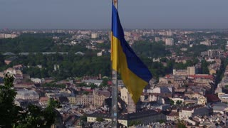 Aerial Shot Ukrainian National Flag Flying on Top of the Beautiful Panorama of the City Lviv. 4k