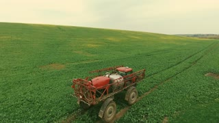Aerial. Tractor spray fertilize field with insecticide herbicide chemicals in agriculture field and evening sunlight