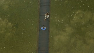 Aerial view Loving Couple on a Wooden Bridge in the Mountains. Morning fog. Slow motion shot
