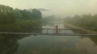 Aerial view Loving Couple on a Wooden Bridge in the Mountains. Morning fog