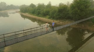 Aerial view. Loving Couple on a Wooden Bridge in the Mountains. Morning fog