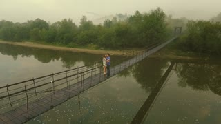 Aerial view Loving Couple on a Wooden Bridge in the Mountains. Slow motion