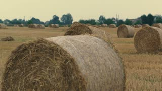 Aerilal Shot Field with Straw Bales Under Sunset Sky zoom footage