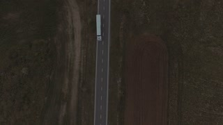 Articulated Truck Road Goes through Fields. Aerial Video