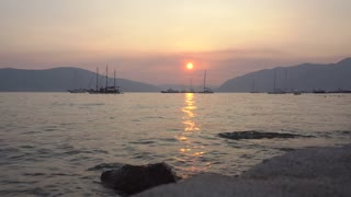 Beautiful evening in Tivat, Montenegro. Time lapse sunset over mountains and sea view of Porto Montenegro. Touristic promenade