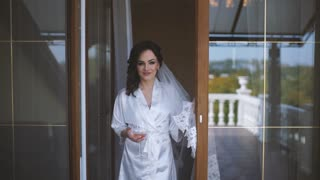Charming Bride in White Transluent Robe Enjoying the View in The Terrac With a Glass of Wine. Slow Motion