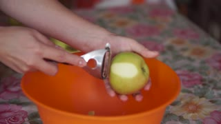 Chef slicing peeled apple at wooden plank in kitchen. Slicing peeled apple. Apple slice. A knife cutting apple in half. Knife cut half apple. Sliced apple is healthy food