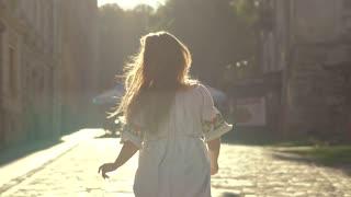 Day shot of a beautiful girl walking behind the sunlight