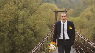 Groom Walking through the Wooden Bridge in the Mountains. Slow motion