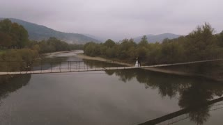 Loving Couple on a Wooden Bridge in the Mountains. Aerial video. Slow motion