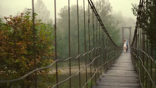 Loving Couple on a Wooden Bridge in the Mountains. Morning fog. Slow motion