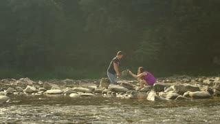 Loving Couple Pours Water on a Mountain River. Sun reflections in the camera lens. Slow motion