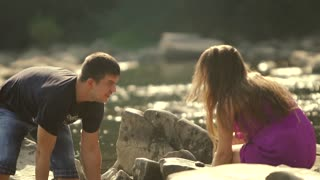 Loving Couple Pours Water on a Mountain River. Sun reflections in the camera lens