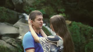 Loving Couple Walking Outdoors Near a Waterfall. Morning light shines into the camera. Slow morion
