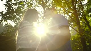 Loving Couple Walking Outdoors Near a Waterfall. Morning light shines into the camera. Slow motion