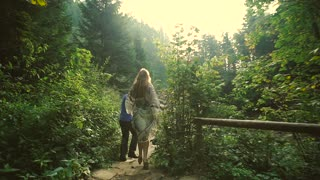 Loving couple walking outdoors near a waterfall. Morning light shines into the camera