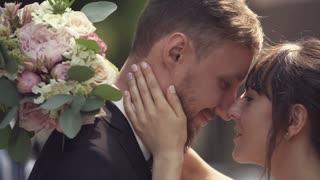 Bridegroom hugs and kisses his wife