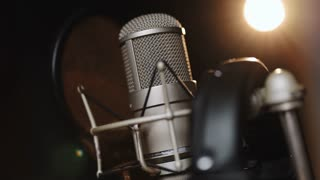 Close-up of microphone on stage against a black background with lighting. Silhouette of the microphone in the dark. Music instrument concept. Podcast, radio, interview, music studio recording