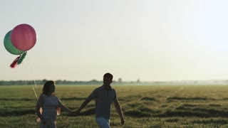 Couple walking in a field and holding hands at sunset. Filmed in slow motion.