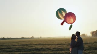 Couple with helium balls walking into the field and holding hands at the sunset