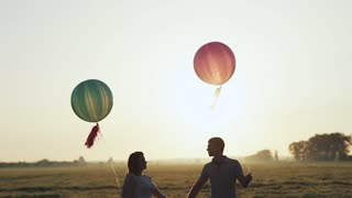 Couple with helium balls walking into the field and kisses at the sunset