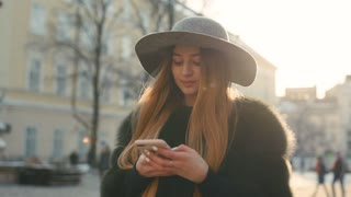 Gorgeous brunette woman in a gray hat standing in the crowded city street and using her phone for texting