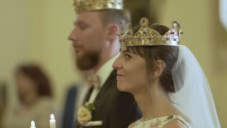 Loving couple standing in the church in crowns with candles in their hands
