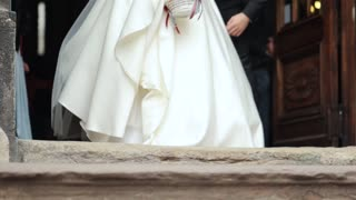 Newlyweds leave the church takes his wife in his hands