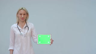 Portrait of a female doctor with white coat and tablet with green screen and stethoscope smiling