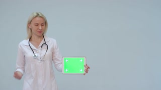 Portrait of a female doctor with white coat and tablet with green screen