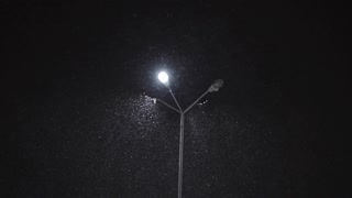 Snow falling by night near a street lamp