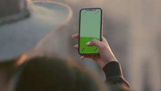 Woman holding green screen smartphone