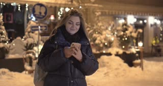 Woman using Mobile Phone During Walk on Streets of Night Town