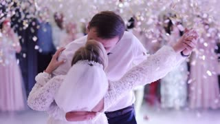 Young beautiful bride and groom dancing first dance at the wedding party shrouded by confetti