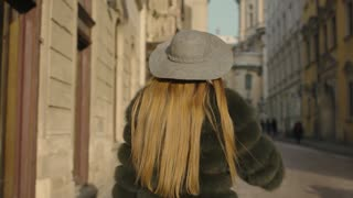 Young woman with long hair, big blue eyes in a gray is rushing in the city-center, than turns to camera and smiles
