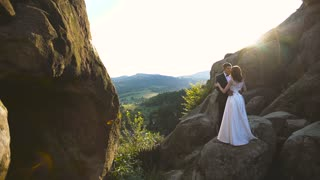 Wedding Bride And Groom Walk in a Rocks. Good sun backlight. Slow motion