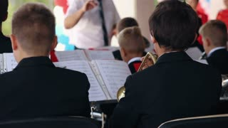 Young guys play on wind instrument in orchestra